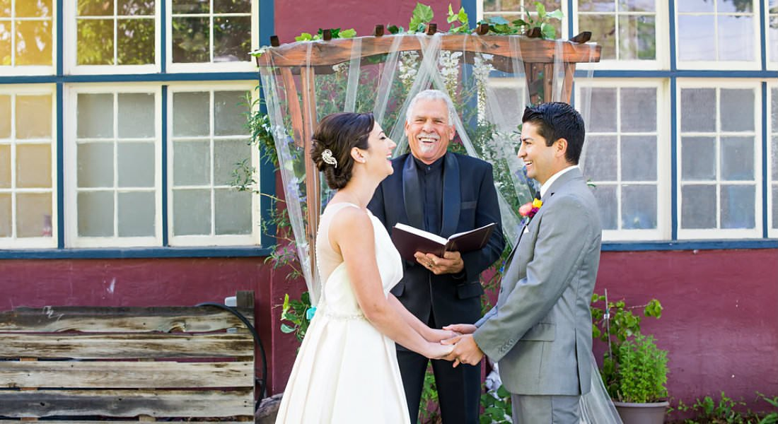 A couple taking their vows outside with a smiling officiant  in front of a decorated arch.