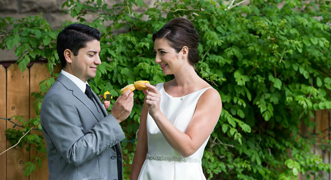 "A young wedding  couple ""toasting"" little cakes in an outdoor setting."