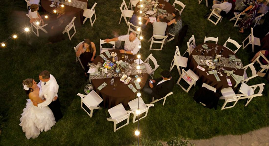 Elevated view of outdoor wedding party with populated tables and dance area.