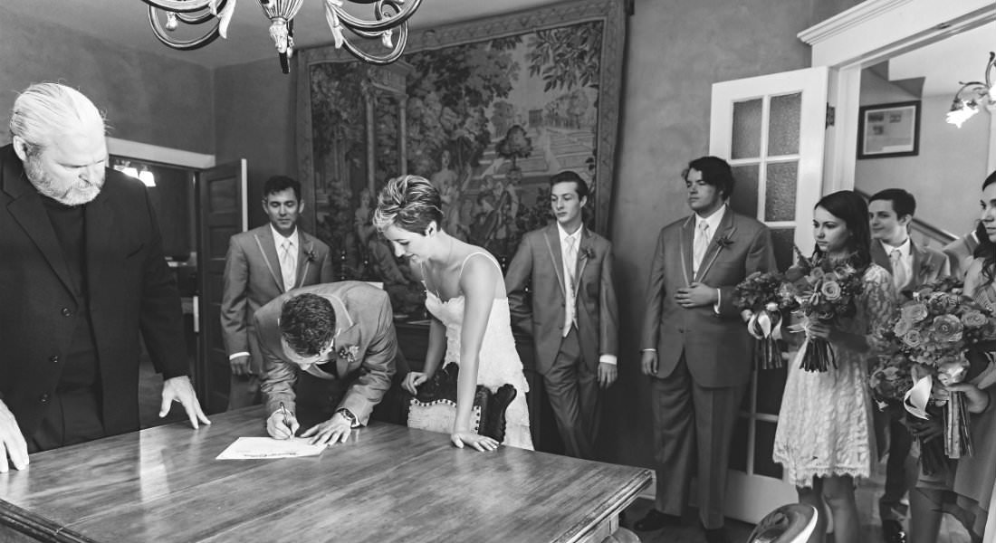 B&W photo of wedding party signing their license with witnesses.