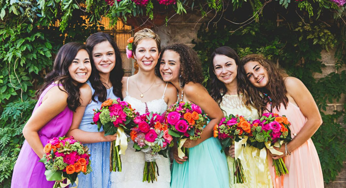A bride and bridesmaids in vibrant colors pose with their floral arragements