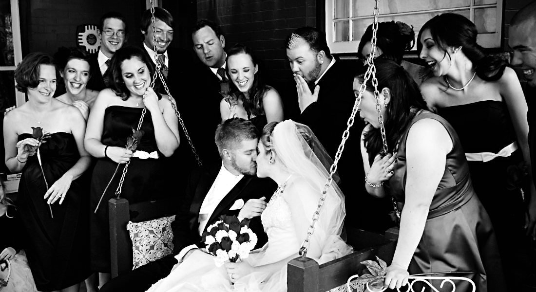 A wedding party looks on as a bride and groom kiss on porch swing.